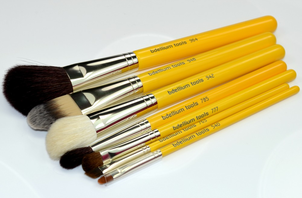 Image of the seven makeup brushes with yellow wooden handles and silver ferrules