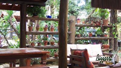 Detalhe da execução do paisagismo com as pranchas de madeira com os pilares de madeira com os vasos de barro no restaurante Recanto das Pedras.