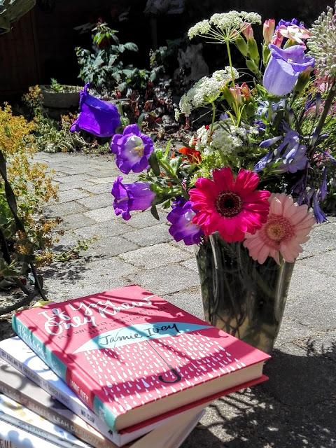Boek If you only knew van Jamie Ivey, liggend in de tuin naast een bos bloemen.