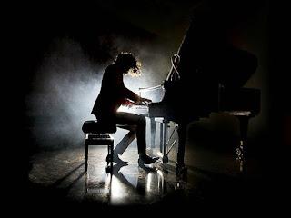 En la oscuridad, un hombre con el pelo largo toca el piano. Un foco al fondo ilumina desde atrás, por lo que solo se ve la silueta del piano y del pianista.