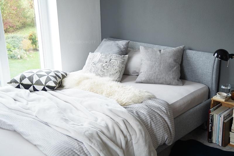 Schlafzimmer im Herbst einrichten und dekorieren in Grautönen und Weiß, mit vielen Wohntextilien für eine gemütliche Atmosphäre und Weinkiste als Nachttisch, Fellen, Kissen, Decken