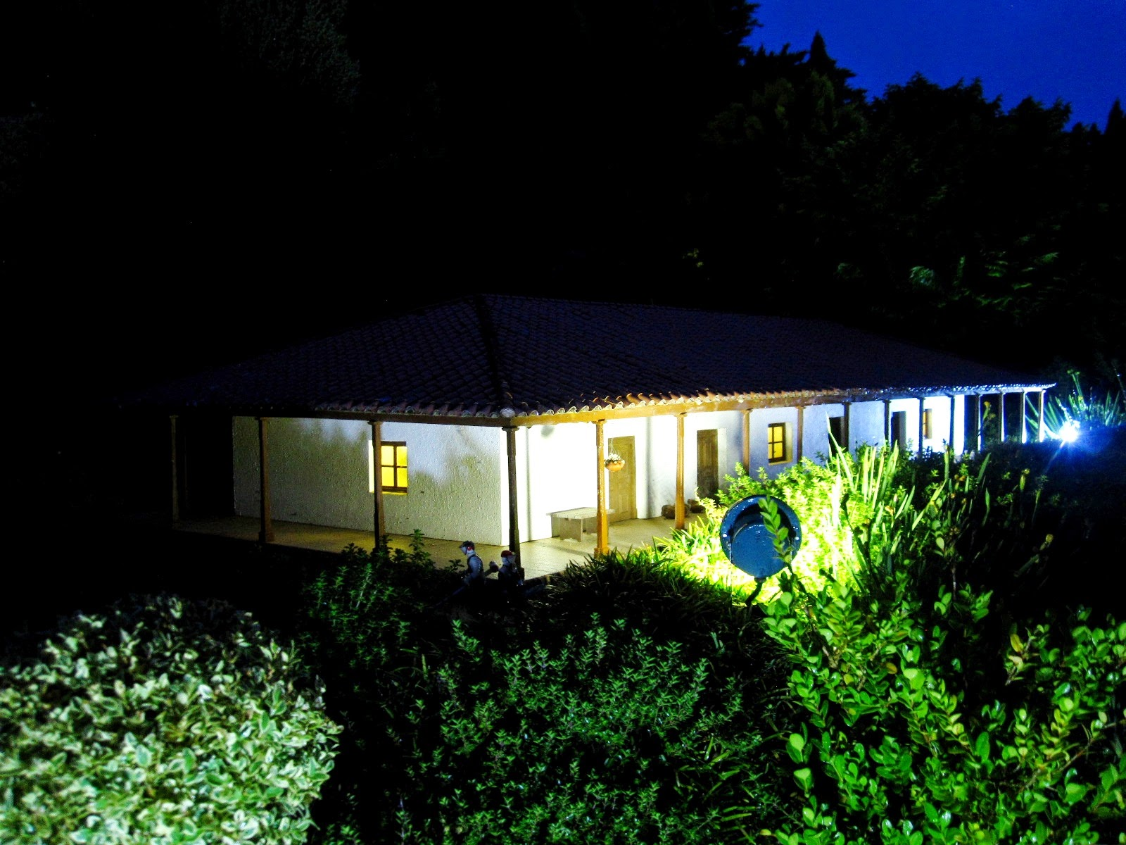 Miniature model of a lit-up building surrounded by bushes, at night.
