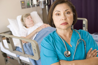 Photo of an unhappy nurse standing near a patient's bedside