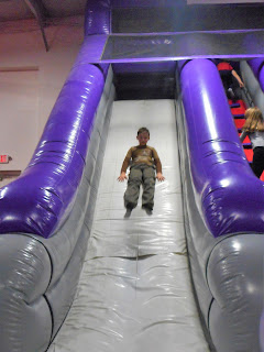 Boy sliding down a gigantic inflatable indoor slide.