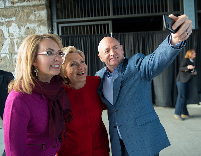 image of former Congresswoman Gabby Giffords, Hillary Clinton, and Giffords' husband Mark Kelly standing together, with Kelly reaching out his arm to take a selfie of the three of them