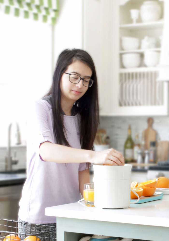 Samantha Garay in kitchen freshly squeezing orange juice