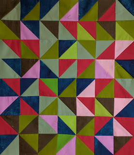 Green, red, navy, brown, grey, and pink triangles form random patterns across this quilt.