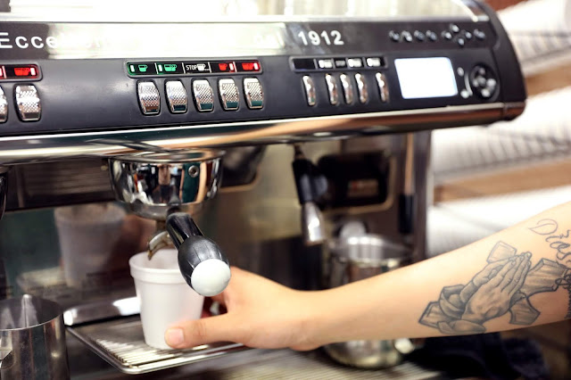 A hand holds a cup under a commercial coffee machine
