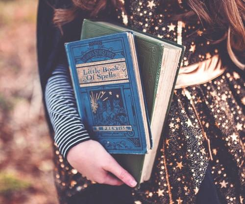 A close up photo of a young girl's arm holding two vintage looking books, one green, one blue reading Little Book of Spells - the girl is wearing a gold and black witch's outfit with stars