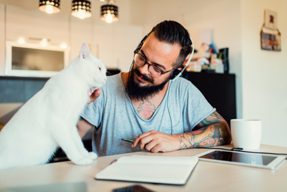 white cat and man with beard at desk