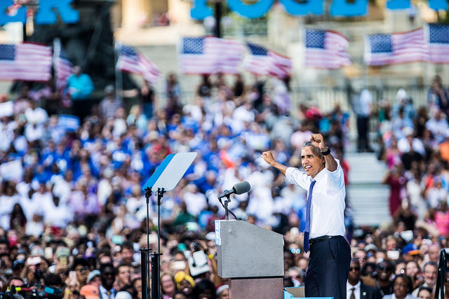 image of President Obama at a Clinton campaign rally, raising his arms in the air in front of a huge crowd