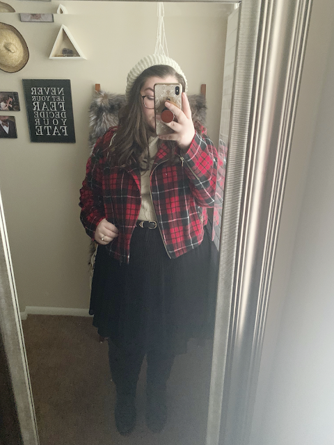 A mirror selfie of an outfit of red plaid moto jacket, cowl neck sweater, black pleated skater skirt, tights and over the knee boots.