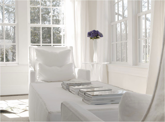 White room with a reading area surrounded by large encasement windows, dueling sofa chairs and books