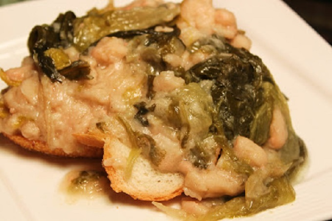 Italian Escarole & Beans is a thick stew like soup that is over Italian day old bread. Also called greens and beans.