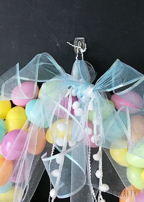 Pastel Easter Egg Wreath DIY - tie wire edge ribbon and pom poms to decorate top of wreath and hang from hook