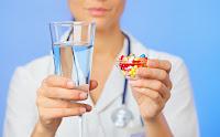 стакан с водой и стакан таблеток