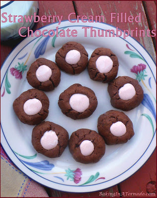 Strawberry Cream Filled Chocolate Thumbprints. Chewy chocolate cookies filled in the center with a gooey sweet strawberry cream. | Recipe developed by www.BakingInATornado.com | #recipe #chocolate