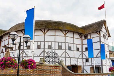 Pic of Shakespeare's Globe Theatre with flags from the outside