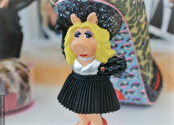 Miss Piggy character heel close up wearing black skirt, painted gloves and ring
