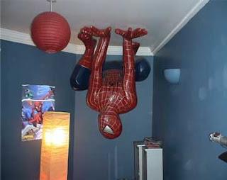 Foto de um boneco em tamanho real do super-herói Homem-aranha preso ao teto de um quarto, de ponta cabeça.