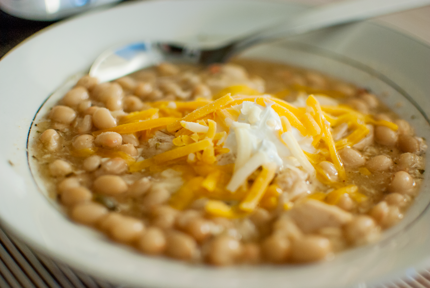 Bowl of White Bean Chicken Chili With Sour Cream and Shredded Cheese