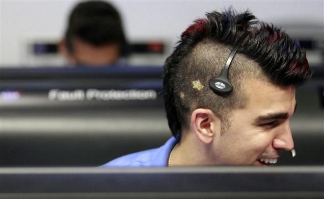 Photo of a NASA engineer who has his hair styled in a mohawk with blue and red highlights. On the side of his skull are two yellow stars.