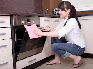 девушка чистить отмывает духовку
