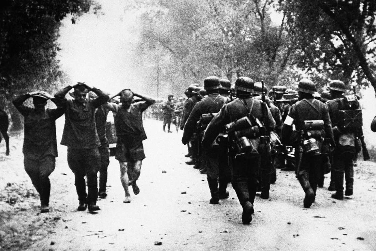 Russian soldiers, left, hands clasped to heads, marched back to the rear of the German lines on July 2, 1941, as a column of Nazi troops move up to the front at the start of hostilities between Germany and Russia.
