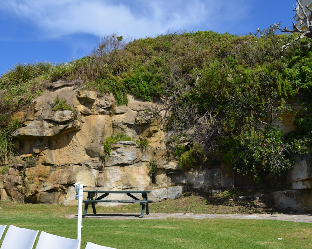 A lawned reserve with picnic tables and park benches is surrounded by sandstone cliffs. The white shapes in the bottom left hand corner are chairs set up to cater for the wedding guests.