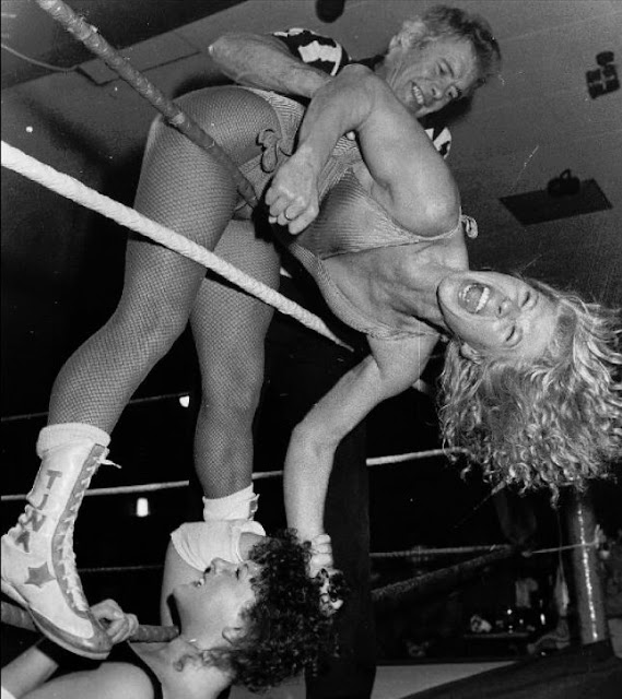 British wrestlers Tina Starr and Nicky Monroe (and the ref) all tangled up in the ropes
