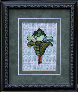 framed embroidery of a stylized flower on canvas in the Arts and Crafts tradition