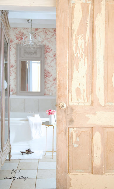 French cottage bathroom with toile and chandelier above bathtub