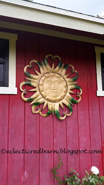 Eclectic Red Barn: Metal sun hanging on the barn
