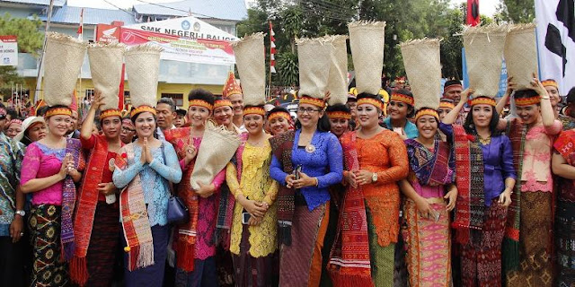 """Peserta karnaval membawa tandok beras di kepala dengan memakai ulos Sadum dan kebaya saat Karnaval Kemerdekaan Pesona Danau Toba di titik awal Soposurung, Balige, Toba Samosir, Sumatera Utara, Minggu (21/8/2016). Perayaan Hari Ulang Tahun (HUT) ke-71 RI tahun ini dipusatkan di Danau Toba, Sumatera Utara dengan tajuk """"Karnaval Kemerdekaan Pesona Danau Toba"""". Acara ini berlangsung di dua tempat yakni Parapat (Simalungun) dan Balige (Toba Samosir)."""