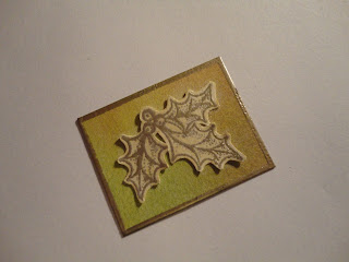 Platinum embossed holly image on coloured mount