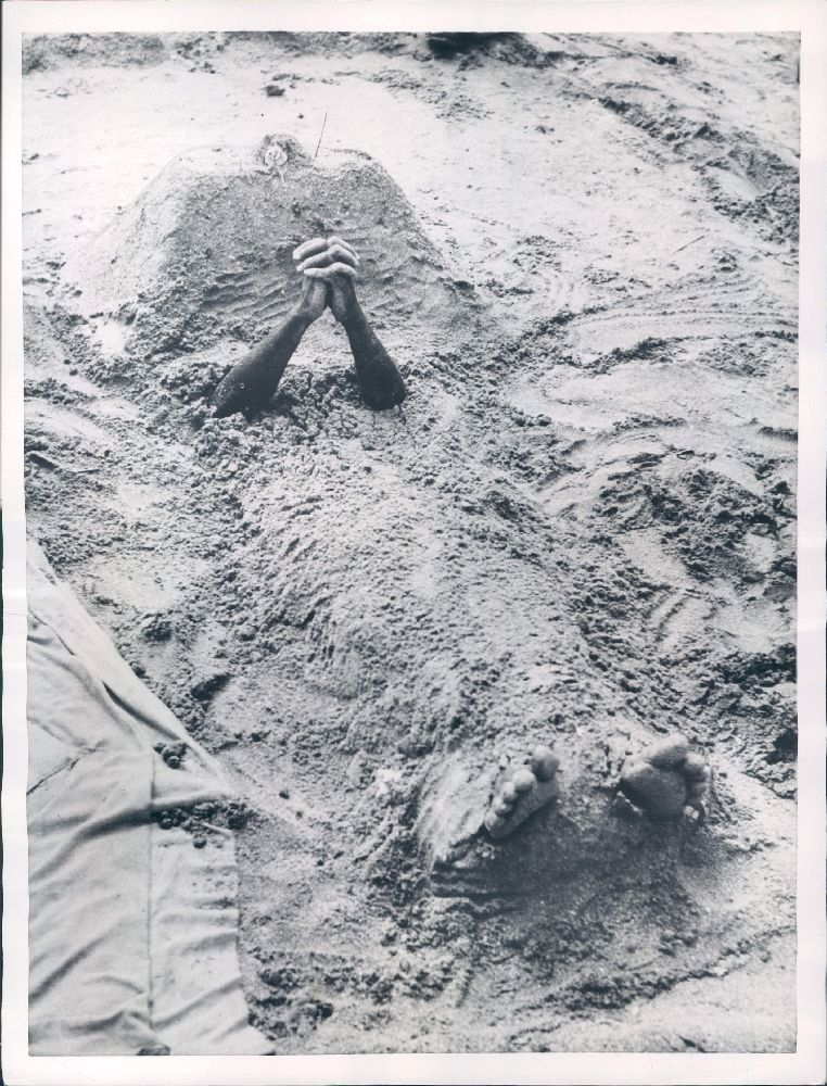 Hindu Man Buried Under Sand Prays to the God of the Rains to Stop the Raining - Bombay (Mumbai) 1953