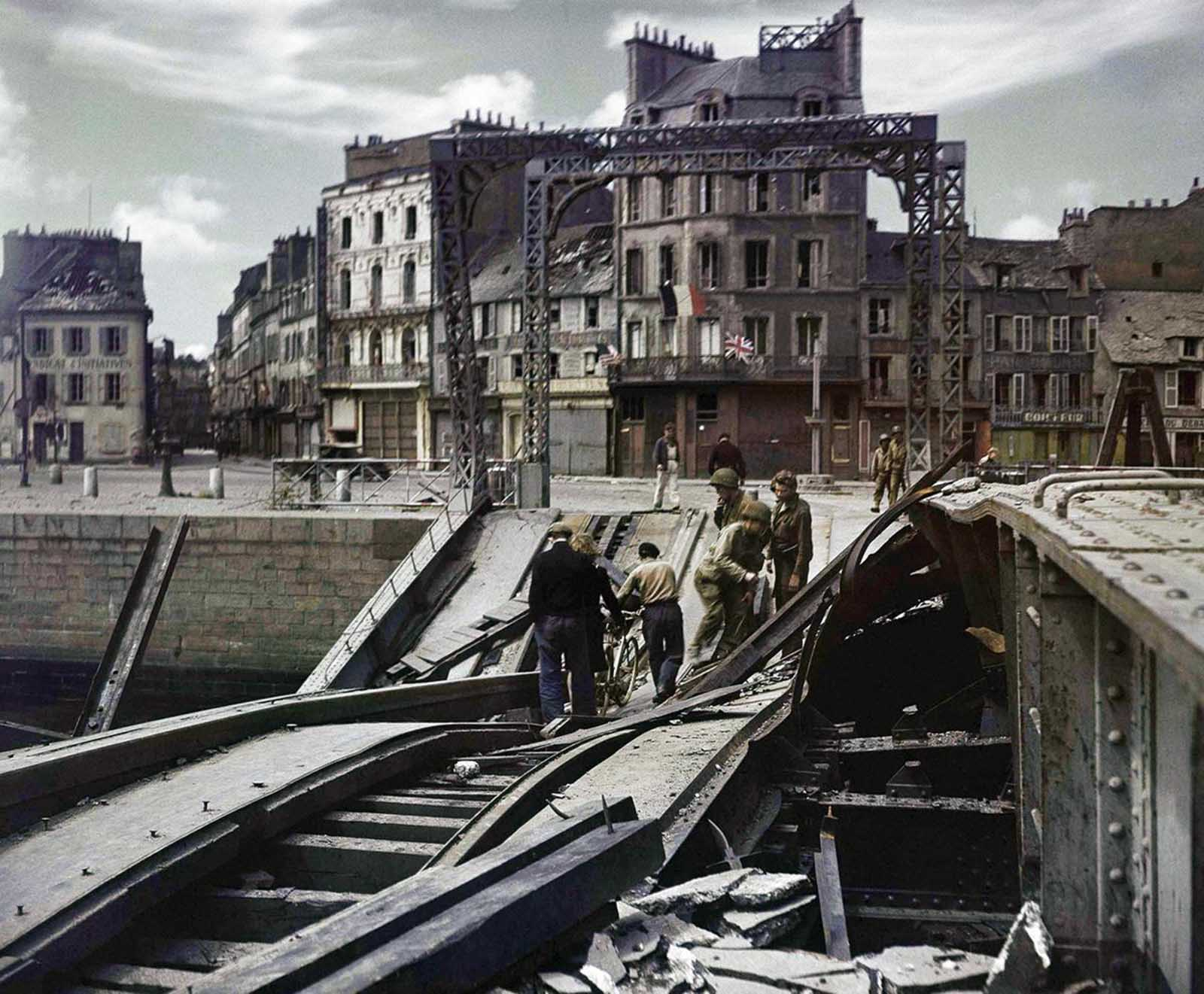 People try to cross a damaged bridge in Cherbourg, France on July 27, 1944.