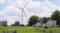 A wind turbine stands over a farmhouse in Adair, Iowa. (Credit: Charlie Neibergall/AP) Click to Enlarge.