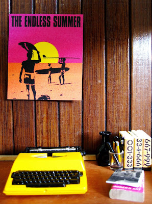 One-twelfth scale modern miniature office with wood-panelled wall, and wooden desk. On the desk is a yellow typewriter, set of yellow books and various pens and pencils in a glass.