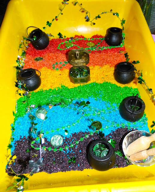 Rainbow bin with rainbow rice, black cauldron, green necklaces, wooden spoons, green coins, and a chest.