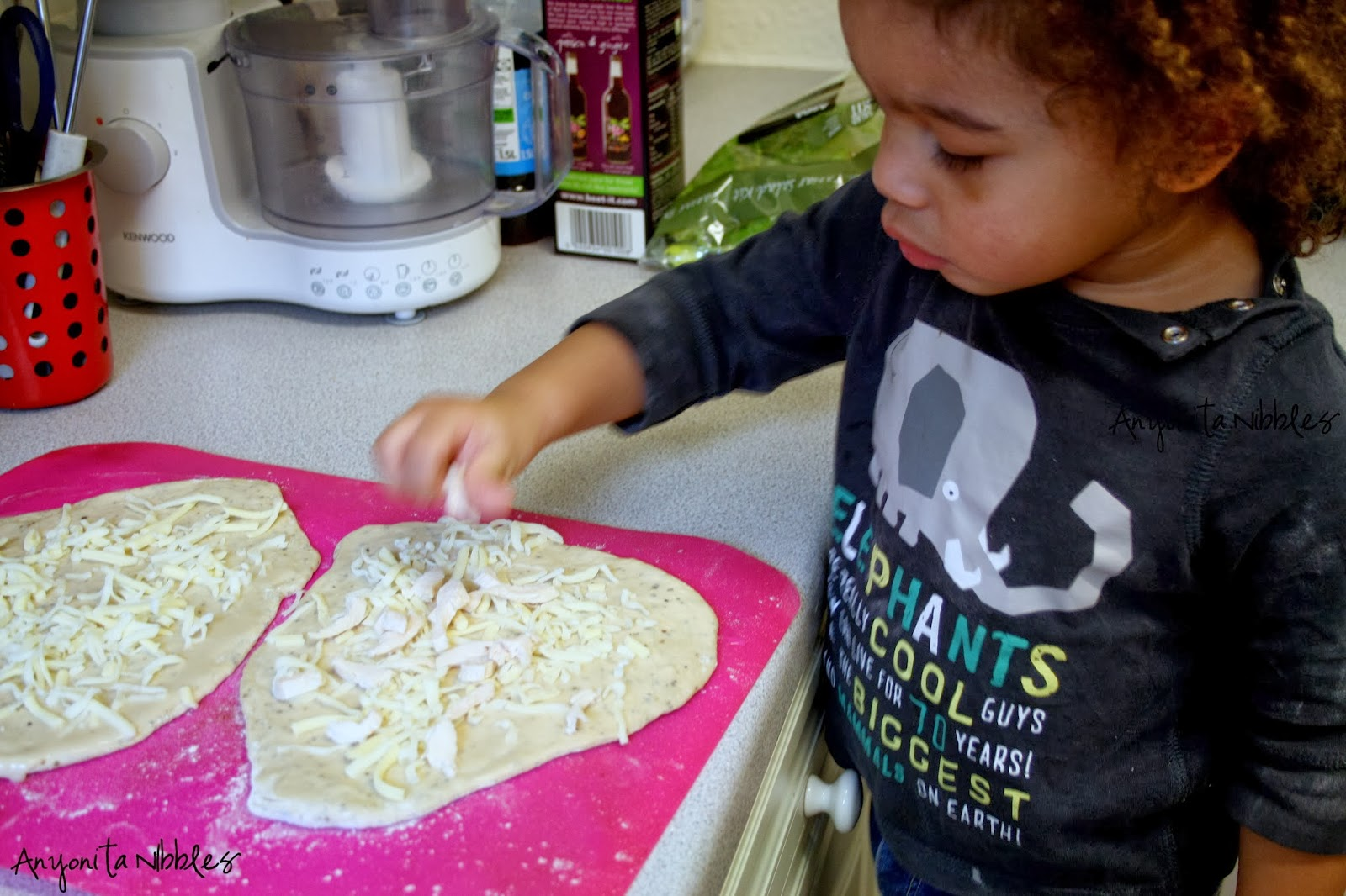 Toddlers who cook: Callum sprinkles cheese onto pizzas | Anyonita Nibbles
