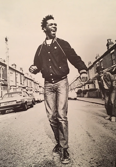 A young Ranking Roger from The Beat smiles widely as he walks down the center of a street in Birmingham. Short row houses are on either side of him and his bandmate Saxa is in the background.
