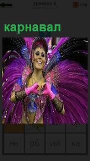 На картинке женщина на карнавале в красивой одежде танцует с длинными перьями за спиной