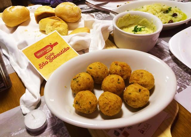 bolinhos de bacalhau servidos com pãezinhos e pasta de grão de bico