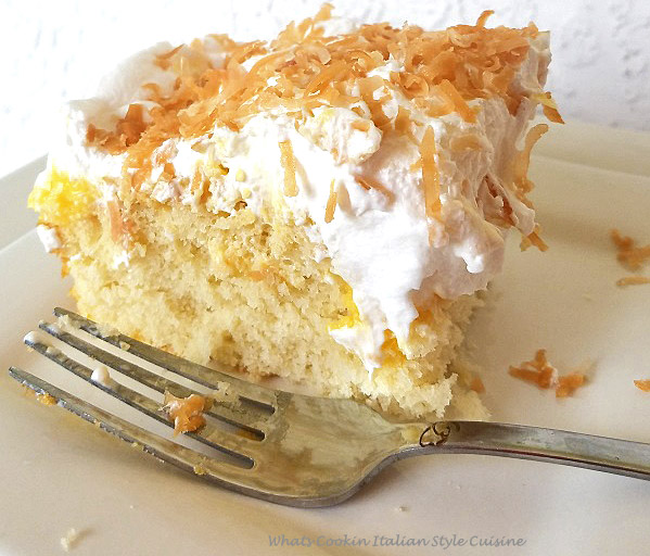 This is a  slice of coconut cake with coconut cream pudding that is called poke cakes because you poke holes in the cakes and the coconut cream pudding is throughout the cake then piled high with whipped cream and toasted coconut on top this recipe shows how to make poke cake