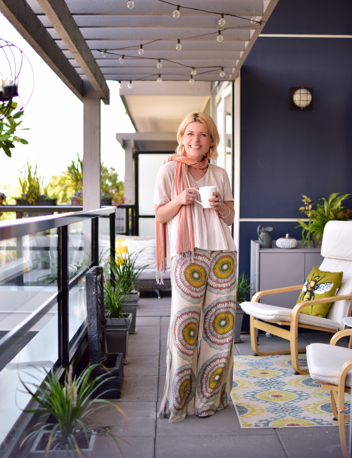 Monika Faulkner styles patterned palazzo pants with a Zara smock top, striped scarf, and platform slides