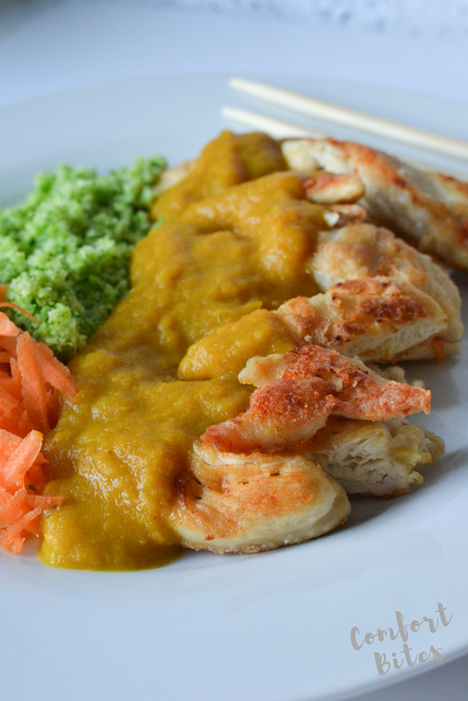 A plate of katsu chicken curry with broccoli rice and shredded carrot