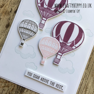 This picture depicts a greetings card at an angle, the card has hot air balloons stamped in Early Espresso, Blushing Bride and Rich Razzleberry using the Lift Me Up stamp set by Stampin' Up!