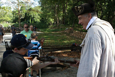 Handling a musket at the American Revolution Museum at Yorktown.