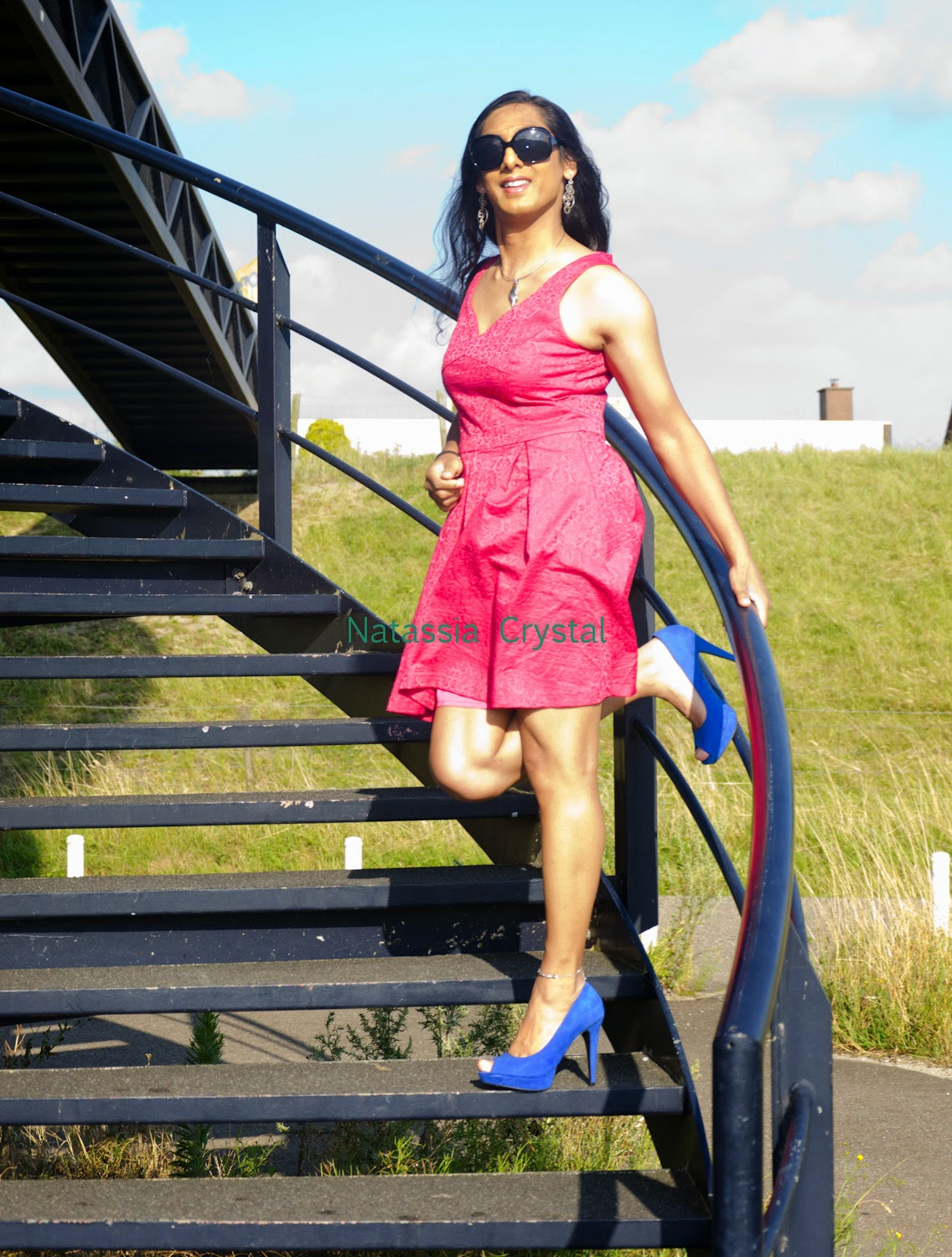 Natassia pink dress blue heels stairs one leg stand